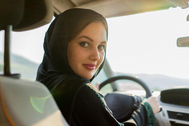 Glückliche moslemische frau, die auto fährt