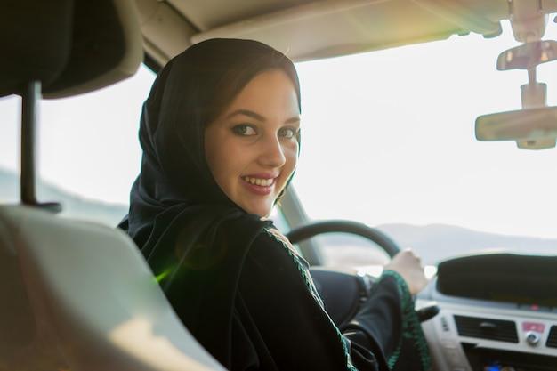 Glückliche moslemische frau, die auto fährt Premium Fotos