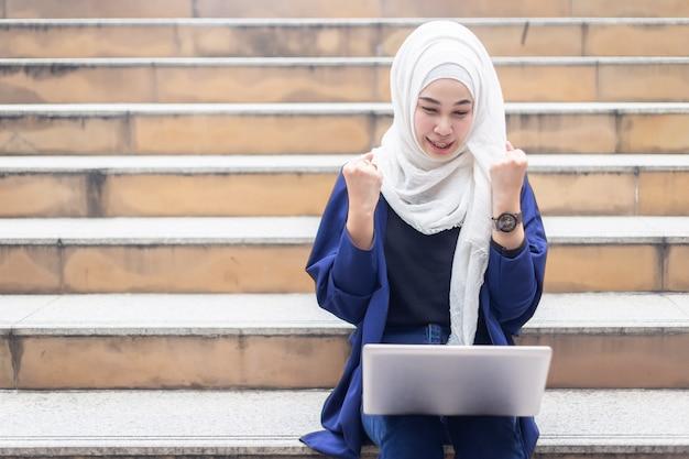 Glückliche moslemische geschäftsfrauen im hijab mit dem laptop, der draußen arbeitet.