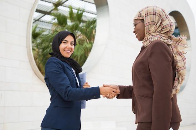 Glückliche moslemische geschäftskollegen, die sich draußen treffen
