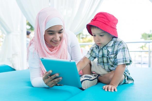 Glückliche moslemische junge frau und kleiner junge auf sommerferien