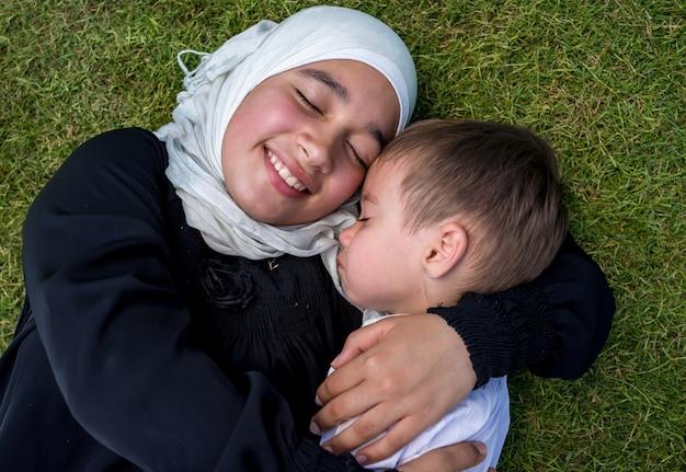 Glückliche moslemische mutter und kind in der natur