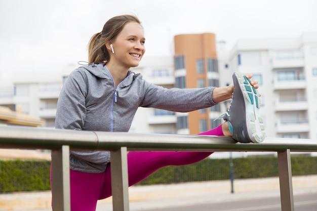 Glückliche motivierte dame, die allein draußen trainiert