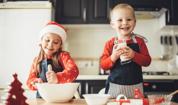 Glückliche mühe und schwester kochen etwas in der küche, während sie sich auf die weihnachtsferien vorbereiten, die weihnachtsmannkleidung tragen