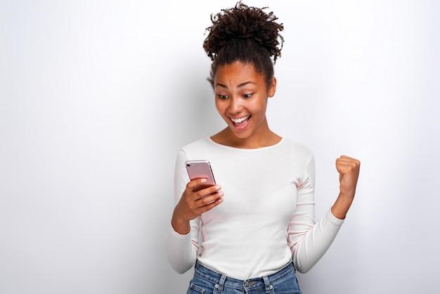 Glückliche mulattefrau, die einen smartphone in ihrer hand hält und mit der siegergeste betrachtet den schirm schreit