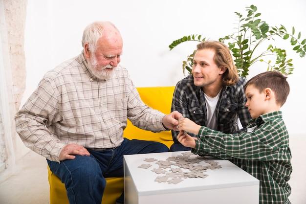 Glückliche multi-generationsfamilie, die zusammen puzzle zusammenbaut