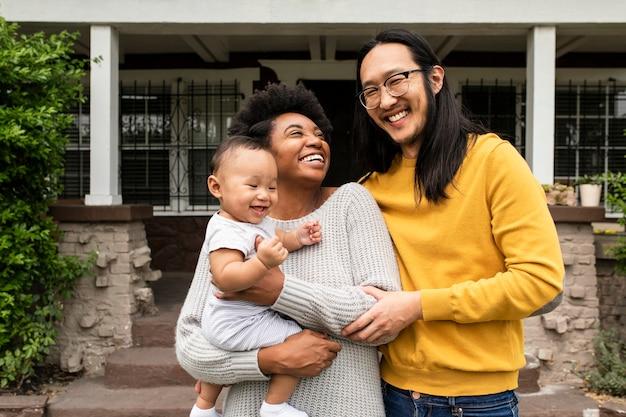 Glückliche multiethnische familie, die während der sperrung von covid19 vor dem haus steht house