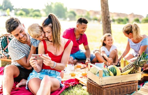 Glückliche multiethnische familien, die bei einer picknick-gartenparty mit telefon spielen