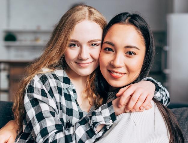 Glückliche multiethnische frauen umarmen