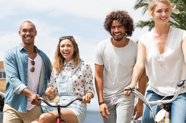 Glückliche multiethnische freunde, die an einem hellen sonnigen tag mit fahrrädern genießen