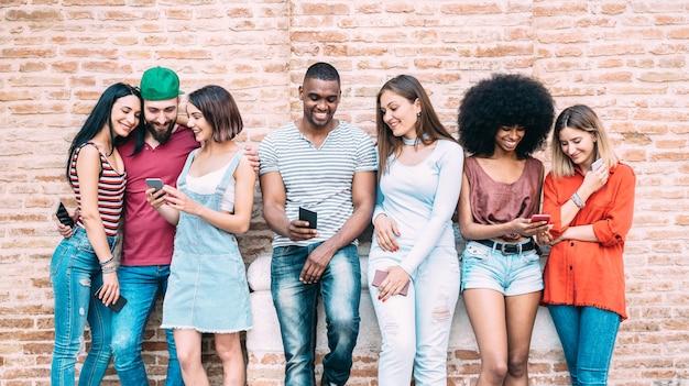 Glückliche multiethnische freunde, die smartphone am hinterhof des universitätskollegs verwenden