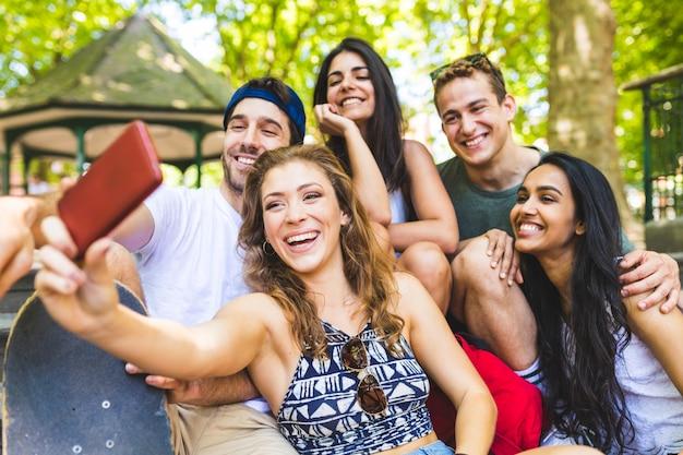 Glückliche multiethnische gruppe freunde, die ein selfie nehmen