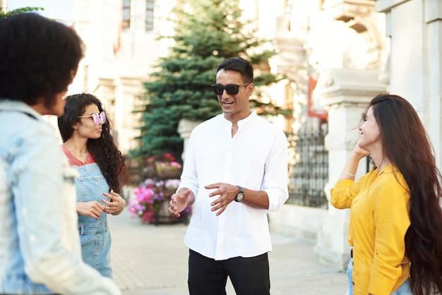 Glückliche multiethnische junge leute entspannen sich zusammen und haben spaß beim reden und plaudern, um ideen auszutauschen.