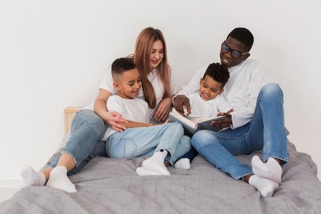 Glückliche multikulturelle familie, die spaß zusammen im bett hat