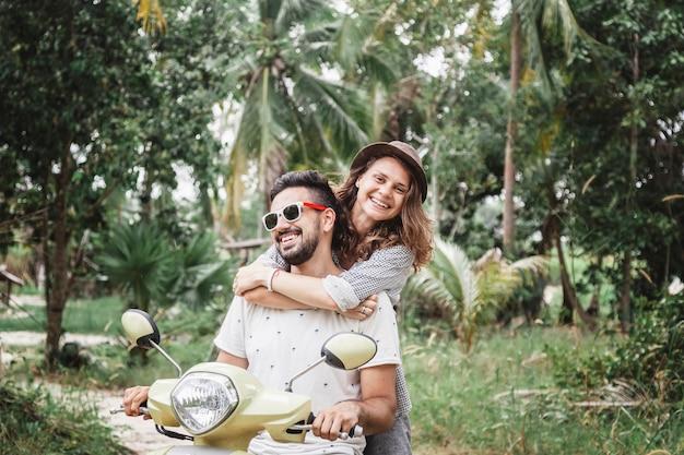 Glückliche multinationale paare, die auf ein motorrad im dschungel, flitterwochen, ferien reisen,