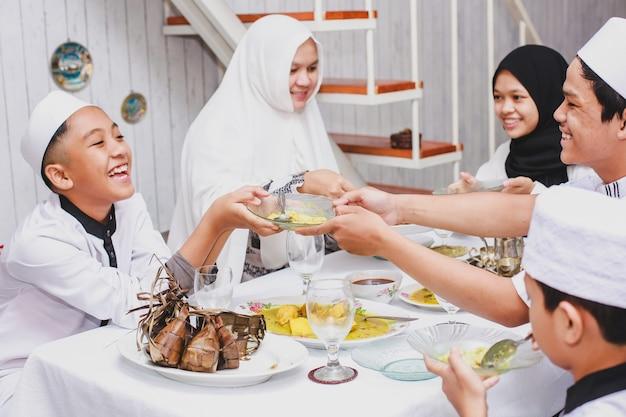 Glückliche muslimische familie, die eid mubarak mit gemeinsamem essen im speisesaal feiert