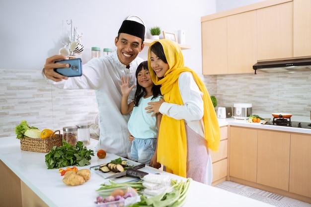 Glückliche muslimische familie, die ein video, ein selfie oder einen anruf zusammen während der iftar-abendessenvorbereitung zu hause mit tochter macht