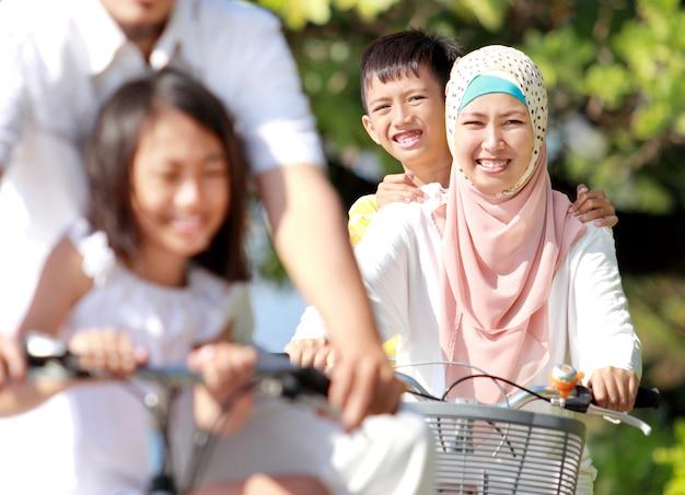 Glückliche muslimische familie, die fahrräder reitet