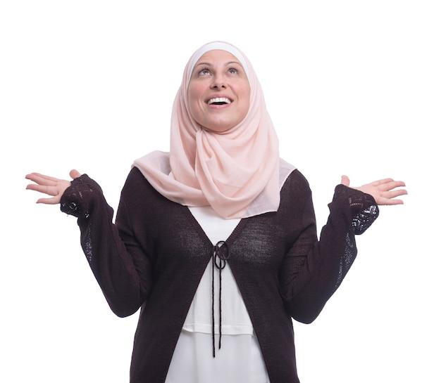 Glückliche muslimische frau, die erfolg über weiße wand feiert