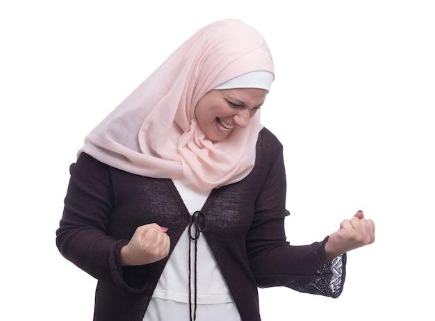 Glückliche muslimische frau, die triumph über weiße wand feiert