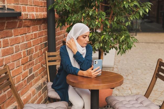 Glückliche muslimische frau mit videoanruf auf dem smartphone im café im freien