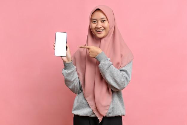 Glückliche muslimische frau zeigt mit zeigefinger auf leeren bildschirm, zeigt modernes gerät, gekleidet in hijab, einzeln auf rosafarbenem hintergrund. technologiekonzept