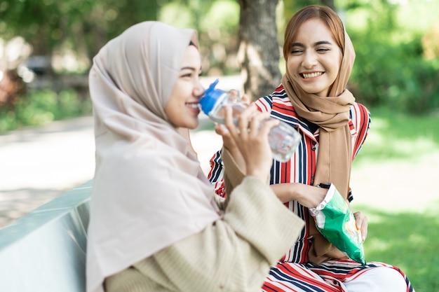 Glückliche muslimische junge frau mit freund genießen ihren snack beim entspannen im park