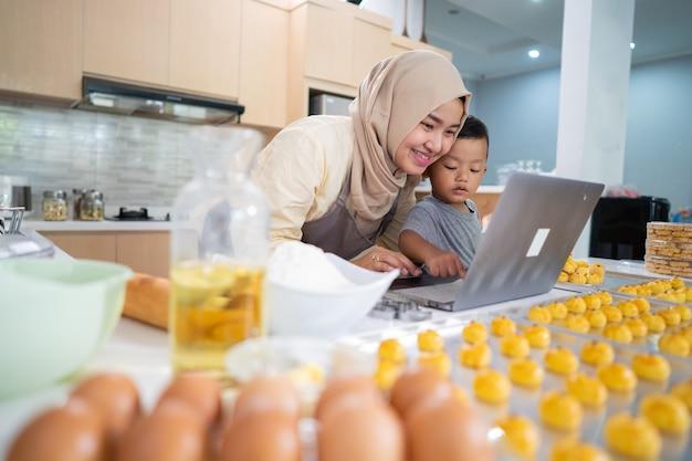 Glückliche muslimische mutter, die von zu hause aus arbeitet und essen bestellt nastar-ananaskuchen für eid mubarak karak