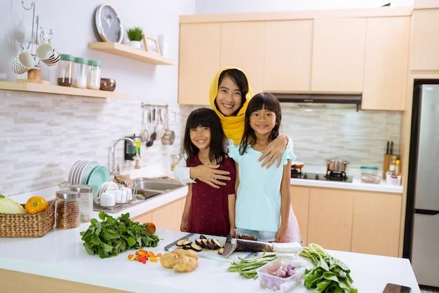 Glückliche muslimische mutter mit ihren zwei reizenden tochter, die zusammen in der küche kochen