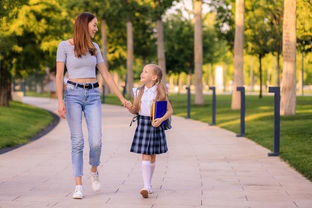 Glückliche mutter bringt kleine tochter schulmädchen zur schule