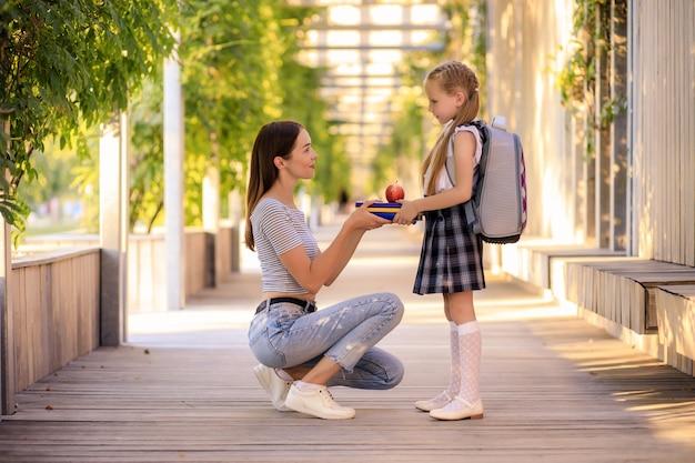 Glückliche mutter bringt kleines schulmädchen zur schule
