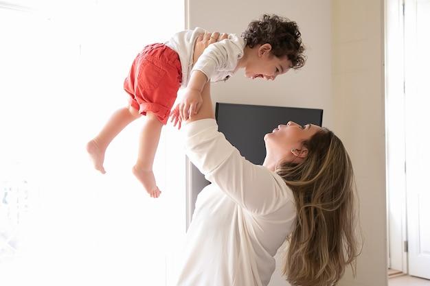Glückliche mutter, die aufgeregtes baby in den armen hält und kind in luft hebt. seitenansicht. elternschafts- und kindheitskonzept