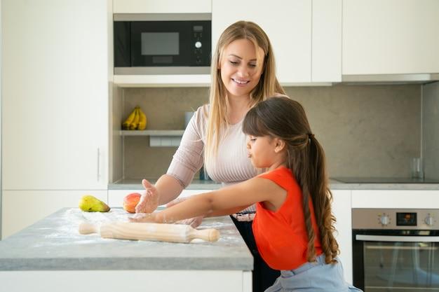 Glückliche mutter, die ihr mädchen beobachtet, das teig am küchentisch knetet. kind und mutter backen zusammen brot oder kuchen. mittlerer schuss. familienkochkonzept