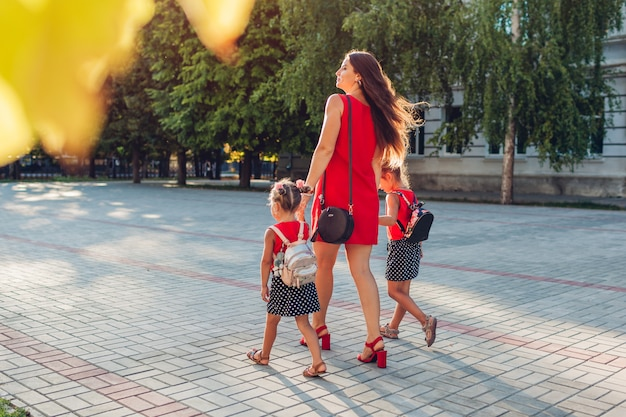 Glückliche mutter, die ihre kindertöchter nach grundschule der klassen draußen trifft. familie geht nach hause. zurück zur schule