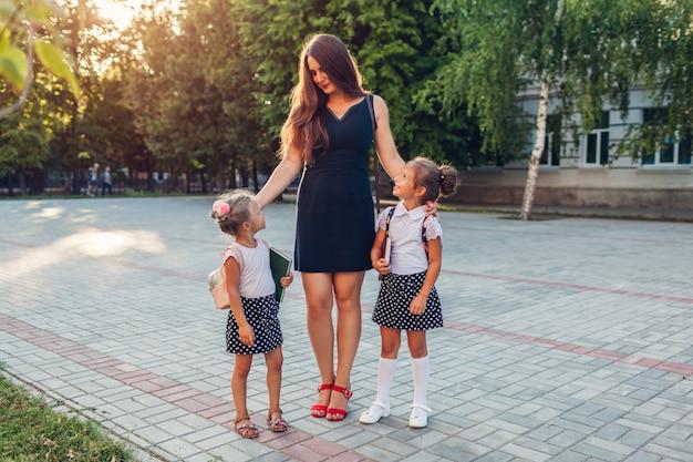 Glückliche mutter, die ihre kindertöchter nach grundschule der klassen draußen trifft.