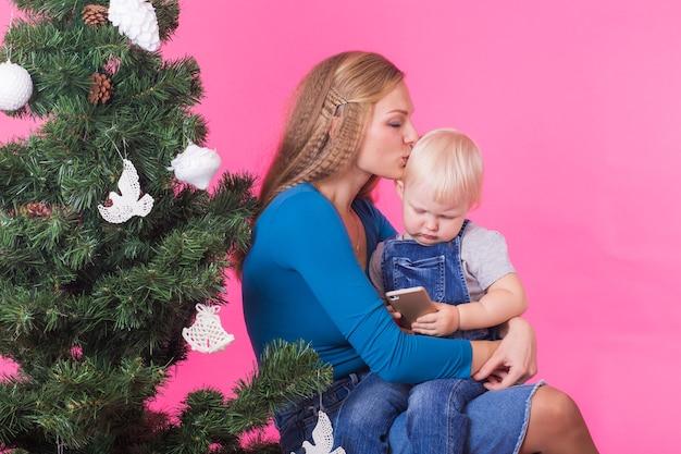 Glückliche mutter, die ihre tochter nahe dem weihnachtsbaum umarmt