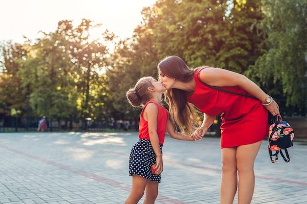 Glückliche mutter, die ihre töchter nach grundschule der klassen draußen trifft. familie küssen. zurück zur schule