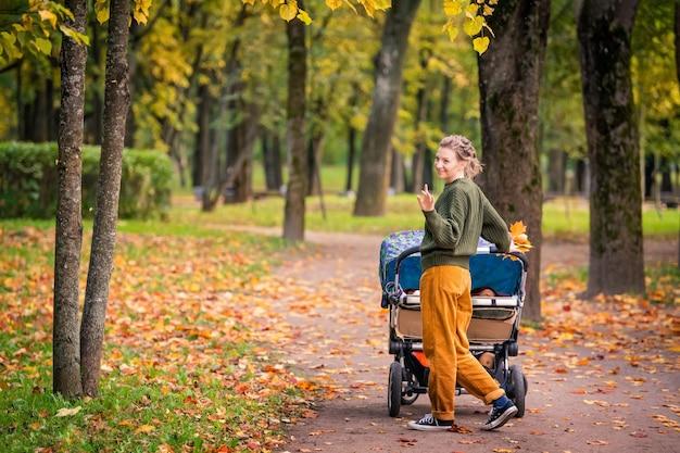 Glückliche mutter, die im herbstpark mit kinderwagen der zwillinge geht