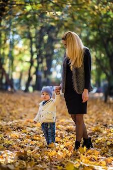 Glückliche mutter, die mit baby im park im herbst spielt. kind lächelt mutter auf händen an