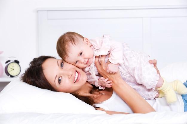 Glückliche mutter, die mit baby liegt
