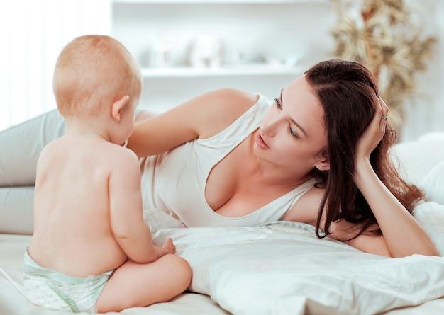 Glückliche mutter, die mit dem baby spricht, das auf dem bett liegt