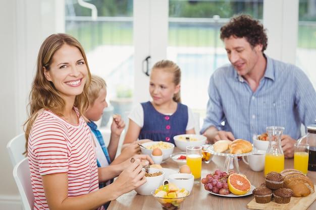 Glückliche mutter, die mit familie bei tisch frühstückt