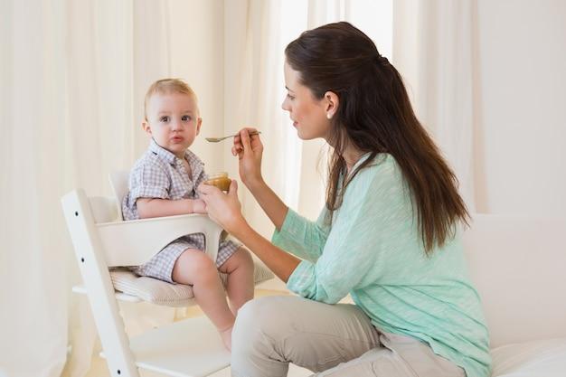 Glückliche mutter, die mit ihrem baby isst