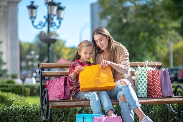 Glückliche mutter, die mit ihrer tochter auf bank sitzt und in einkaufstasche schaut