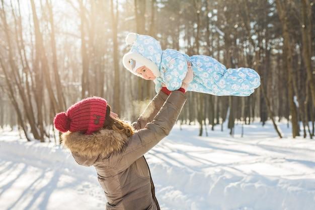 Glückliche mutter, die mit kleinem kindsohnjunge in der winternatur spielt
