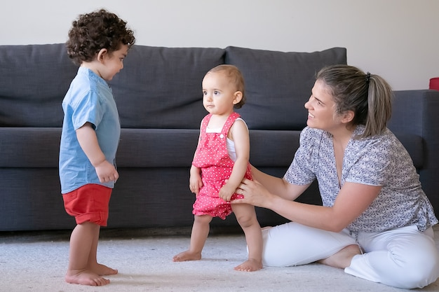 Glückliche mutter, die mit kleinen kindern zu hause spielt und mit gekreuzten beinen sitzt. nettes baby und junge, die barfuß auf teppich im wohnzimmer stehen. familienhaus, wochenend- und kindheitskonzept
