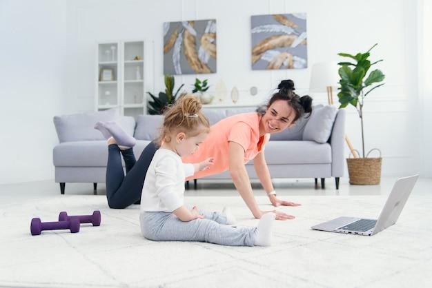 Glückliche mutter, die morgenübungen in der yoga-pose macht, während ihre kleine tochter zu hause spielt. junge entzückende mutter, die spaß daran hat, meditation zu üben, die sich am stressfreien wochenende mit baby entspannt.