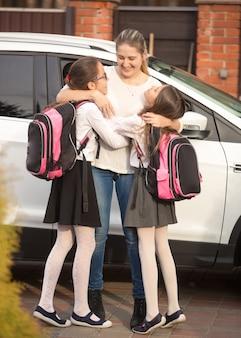 Glückliche mutter, die nach der schule töchter in der nähe des autos trifft