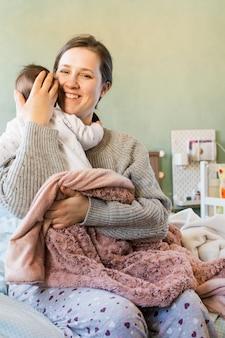 Glückliche mutter, die nettes baby umarmt