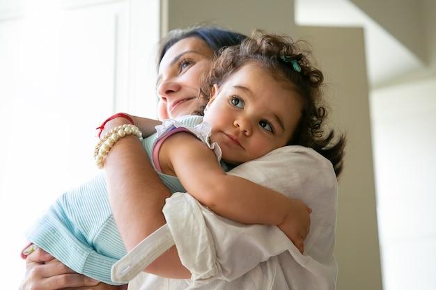 Glückliche mutter, die süße kleine tochter in den armen umarmt und hält. nettes lockiges kleines mädchen, das mutter ansieht. elternschafts- und kindheitskonzept